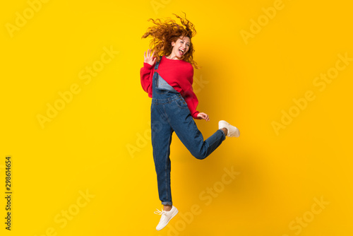 Obraz na płótnie Redhead woman with overalls jumping over isolated yellow wall