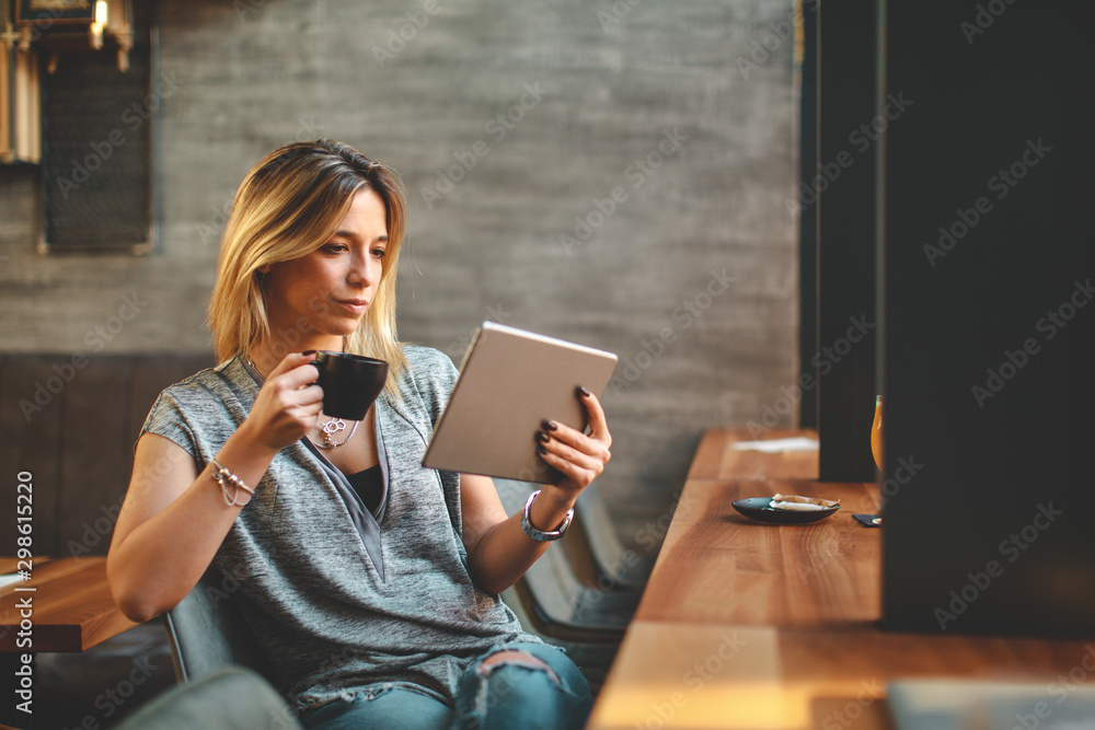 Fototapeta Young beautiful woman relaxing in coffee shop reading electronic book via internet on digital tablet and drink coffee