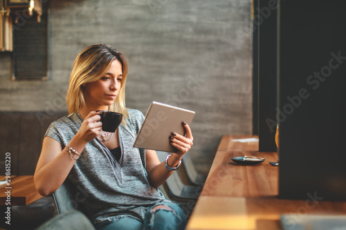 Young beautiful woman relaxing in coffee shop reading electronic book via internet on digital tablet and drink coffee - 298615220