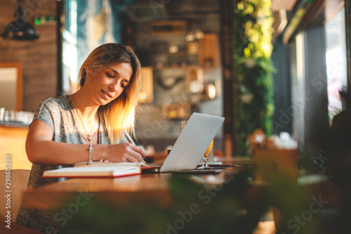 Young woman writing a note with pen with laptop on table at a coffee shop.