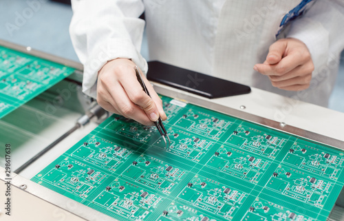 Fototapeta  Technician assembling electronic product by inserting components into board