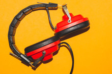 Vintage Red Headphones On Yellow Background. Classic Earphones