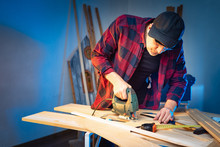 Work In A Carpentry Workshop. A Man Works With An Electric Jig Saw. A Man Is Sawing Parquet. Wood Processing. Work In The Furniture Workshop. Furniture Manufacturing. Concept - Construction Tools