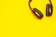 Leinwanddruck Bild - Black wireless headphones on a yellow background
