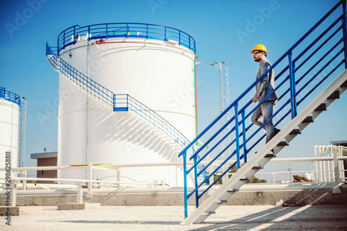 Cuadros en Lienzo Full length of handsome Caucasian businessman in suit and helmet on head going down the stairs on oil tank storage