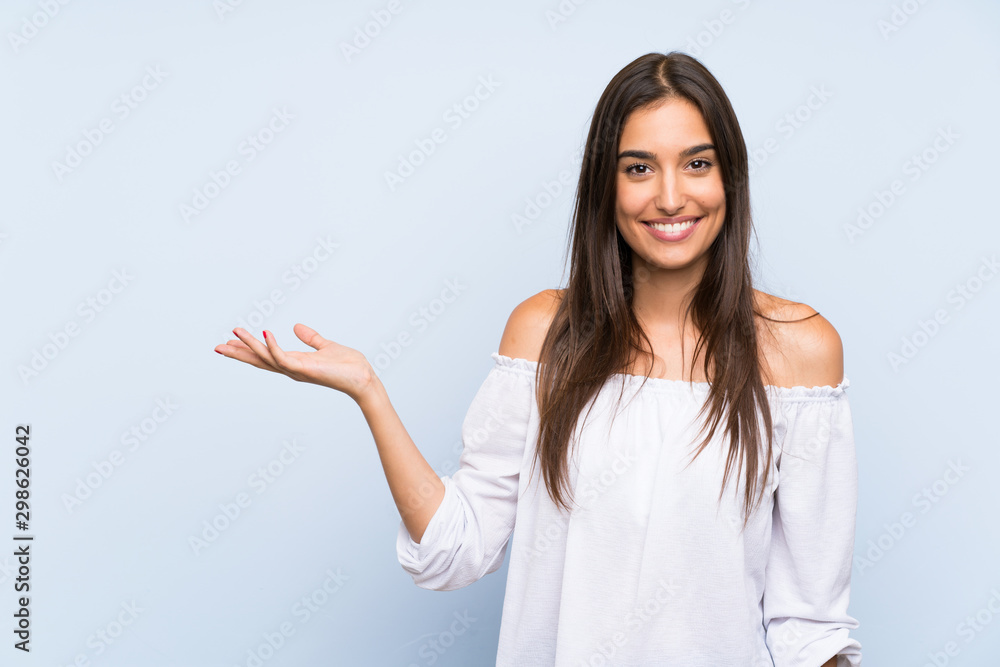 Fototapeta Young woman over isolated blue background holding copyspace imaginary on the palm