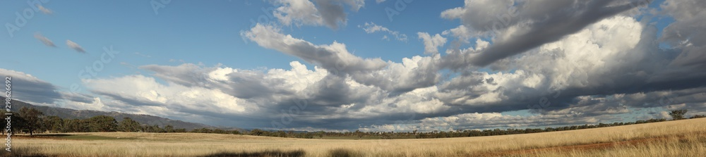 Fototapety, obrazy: Panoramic view of large open dry drought affected farm fields under stretching cloud filled blue skies over properties in rural New South Wales, Australia