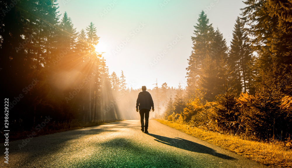 Fototapeta man walking on country road at sunset