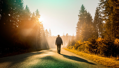 man walking on country road at sunset