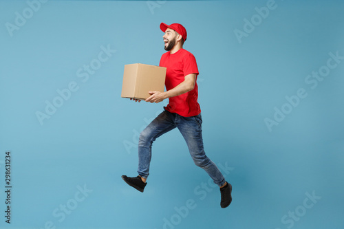 Fotografia Delivery man in red uniform isolated on blue background, studio portrait
