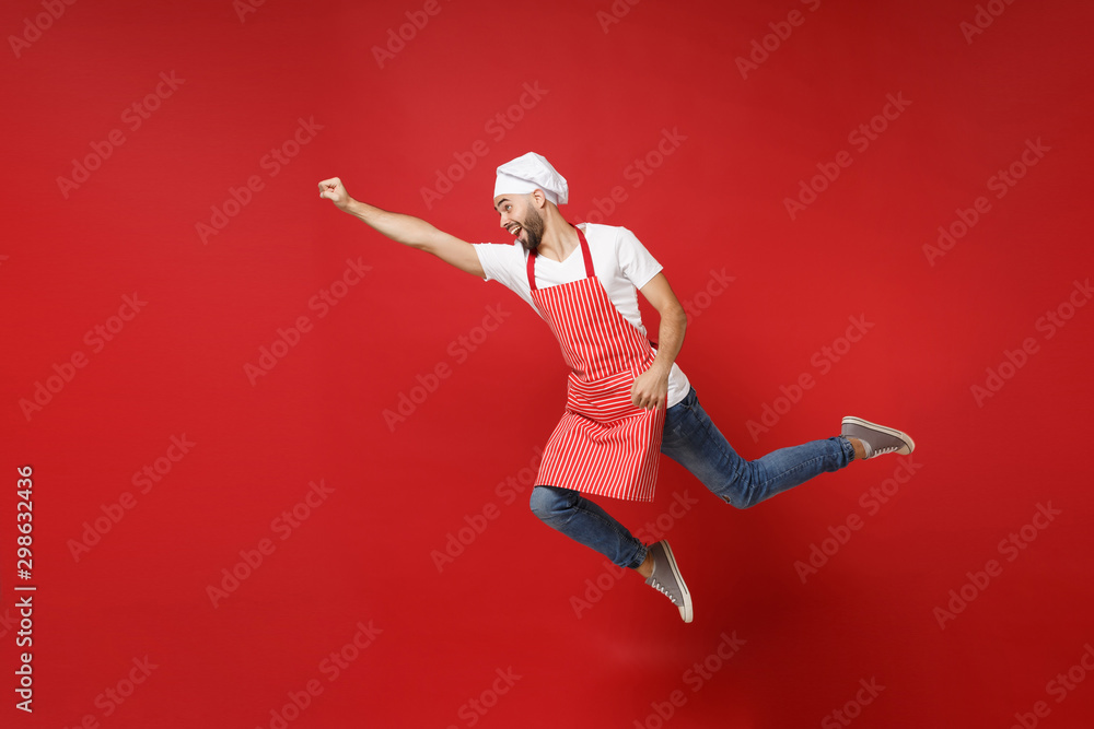 Fototapeta Crazy young male chef cook or baker man in striped apron white t-shirt toque chefs hat posing isolated on red background. Cooking food concept. Mock up copy space. Jumping, fooling around, having fun.