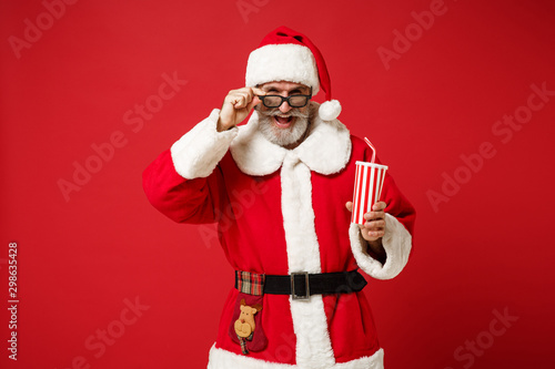 Photo Funny elderly gray-haired mustache bearded Santa man in Christmas hat 3d imax glasses isolated on red background