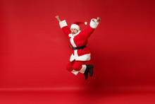Funny Elderly Gray-haired Mustache Bearded Santa Man In Christmas Hat Posing Isolated On Red Wall Background. Happy New Year 2020 Celebration Holiday Concept. Mock Up Copy Space. Jumping, Having Fun.