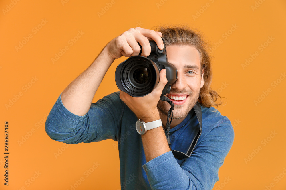 Fototapety, obrazy: Young male photographer on color background