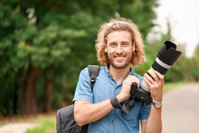 Young Male Photographer With Camera Outdoors