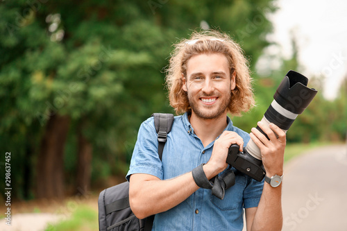 Obraz Young male photographer with camera outdoors - fototapety do salonu