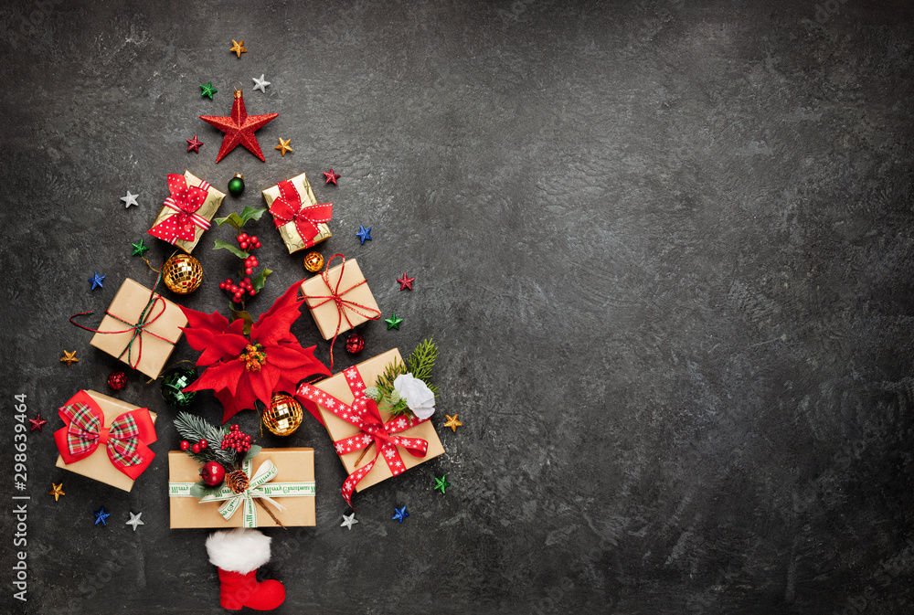 Fototapeta Christmas tree made from Christmas gifts and decorations on black background. Creative winter holiday concept. Flat lay.