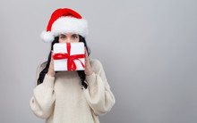 Young Woman With Santa Hat Holding A Gift Box On A Gray Background