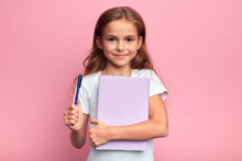 Girl Holding A Book , Pen. Back To School Concept.isolated Pink Background, Studio Shot. Lifestyle, Free Time, Kid Is Ready To Study.