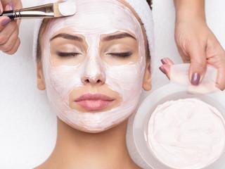 woman receiving facial mask in spa beauty salon
