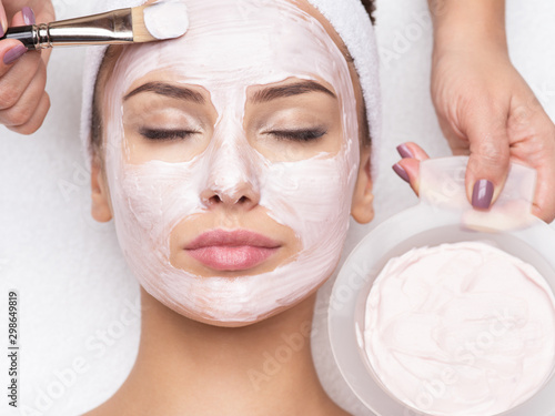 woman receiving  facial mask in spa beauty salon - fototapety na wymiar