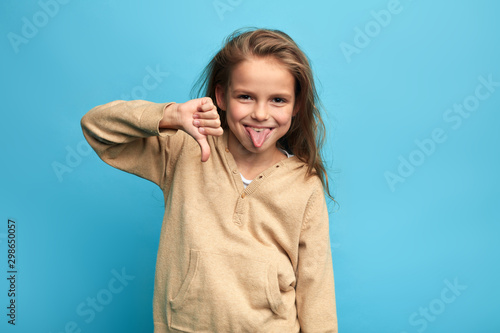 Obraz na płótnie funny crazy girl gesturing thumbs down and sticking out her tongue isolated over blue background