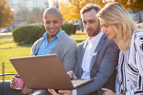 Foto  Mature business people browsing online together, using computer on their meeting