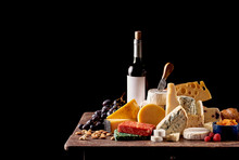 Various Types Of Cheese And Bottle Of Red Wine On Rustic Wooden Table