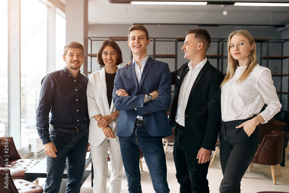 Fototapeta young creative business team leading with a clever boss who is standing with folded arms, close up photo. lifestyle, free time, spare time