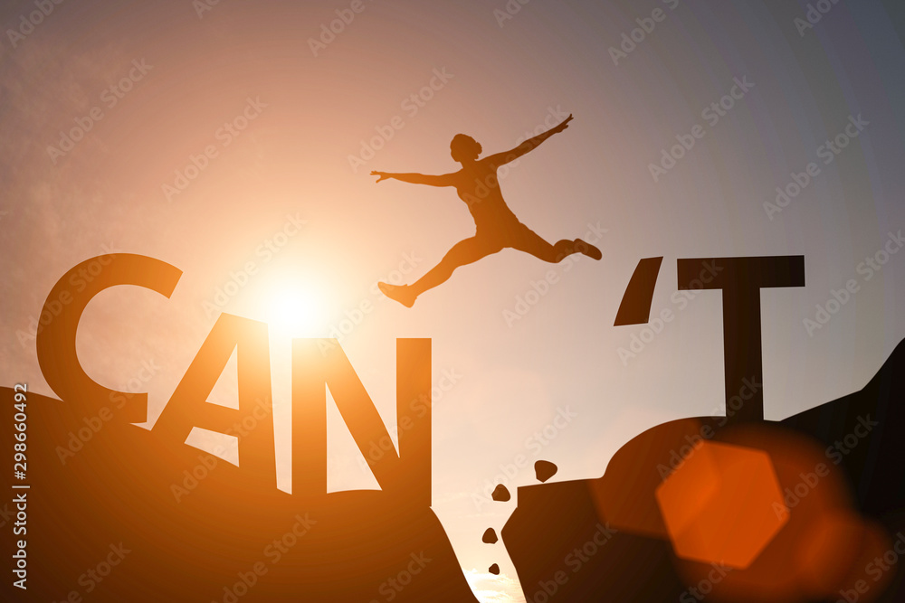 Fototapeta Silhouette man jump between can't wording and can wording on mountain. Mindset for career growth business.