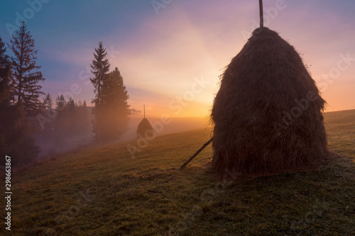 Foto auf Gartenposter Dunkelbraun Beautiful sunrise over mountain foggy hills. Scenic landscape with sun, rising over Carpathian mountains. Haystack on grassland hill on foreground.