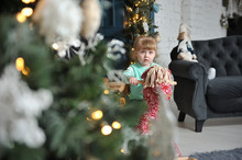 Little Cute Girl Child Sitting On A Red Rocking Horse On A Background Of Christmas Interior