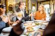Elegantly dressed people having a festive dinner indoors