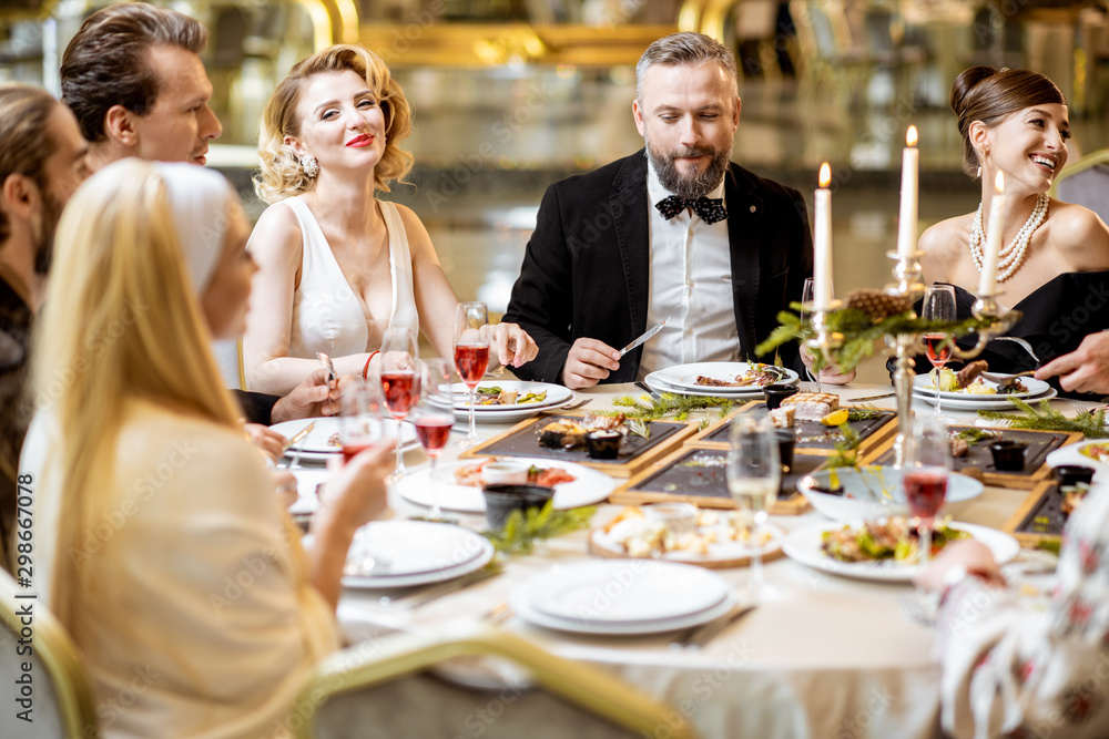 Fototapety, obrazy: Elegantly dressed people having a festive dinner indoors