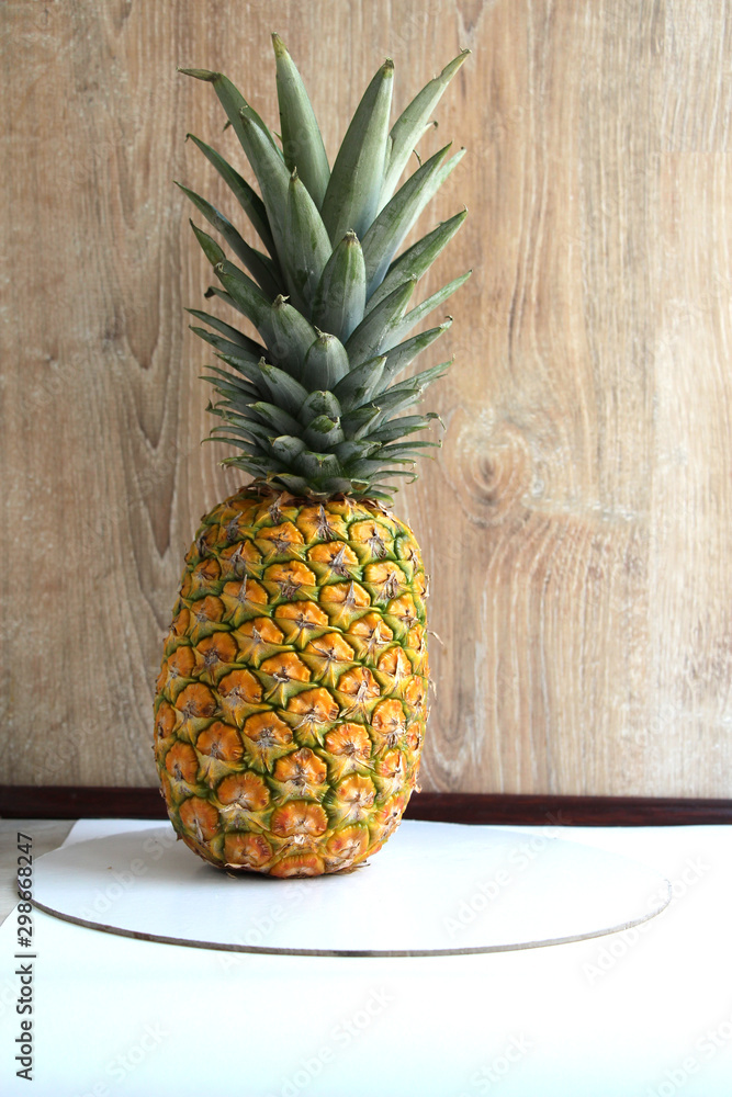 Fresh ripe pineapple (Ananas comosus) on a wooden background. Yellow-orange fruit with green leaves.