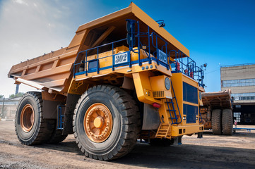 heavy yellow quarry dump truck at repair station at sunny cloudless day