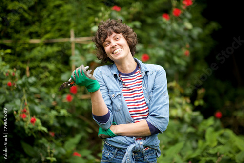 Tablou Canvas laughing female gardener standing with scissors in garden