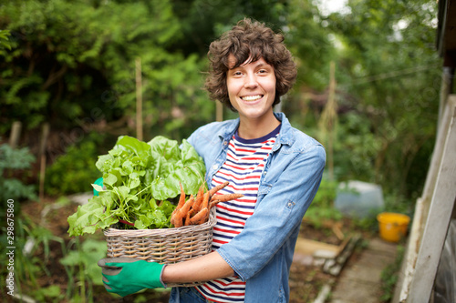 Foto smiling farmer with bunch of vegetables in basket