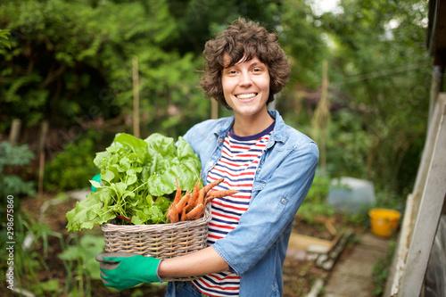 smiling farmer with bunch of vegetables in basket Fototapet