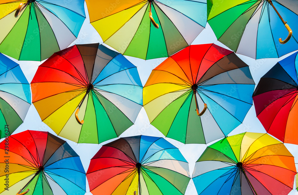 Fototapety, obrazy: a collection of open umbrellas floating in the air, each umbrella is painted in all colors of the rainbow, photographed from below
