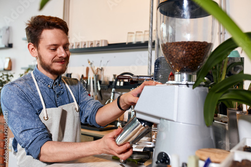 Positive optimistic man in apron, stands pressing on grinder, holds metal coffee pot, expressis gladness, satisfied with job, preparation concept - 298688821