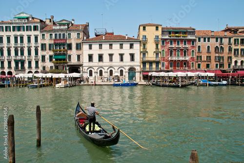 Türaufkleber Gondeln Venice, Italy: Gondolier enters his gondola in the Grand Canal nearby Rialto Bridge
