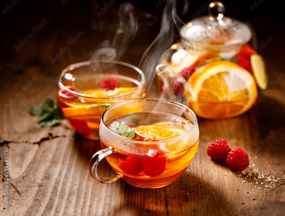 Fototapeta Fruit hot tea with the addition of oranges, lemons, mandarins and raspberries in a glass cups on a  wooden table. Healthy hot drink