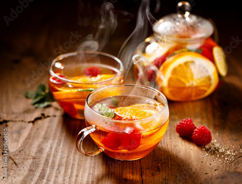 Spoed Foto op Canvas Thee Fruit hot tea with the addition of oranges, lemons, mandarins and raspberries in a glass cups on a wooden table. Healthy hot drink
