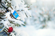 Oklahoma Flag. Christmas Tree Branch With A Flag Of Oklahoma State. Xmas Holidays Greetings Card. Winter Landscape Outdoors.
