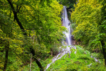 Germany, Impressive 37m high waterfall of climatic spa region in green forest of bad urach in swabian jura nature landscape, a popular tourist attraction