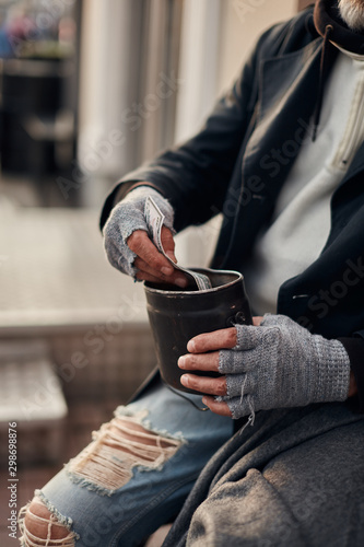 Valokuva  Pity hands of vagrant in grey gloves holding can for collecting money