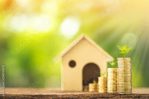 Foto Home model and stack coin with working capital management and plant growing with savings money put on the wood in the public park, Business investment and loan for real estate or buy house concept