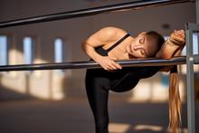 Beautiful Pretty Art Gymnast Puts Leg On Metal Bar, Bent Ahead, Performing Art Gymnastics Element, Training For World Competition, Fitness Health Concept