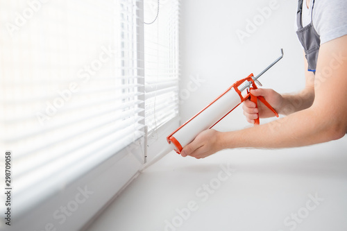 Obraz Construction worker use gun silicone tube for repairing and installing window in house - fototapety do salonu